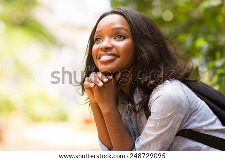 attractive female african college student daydreaming - stock photo