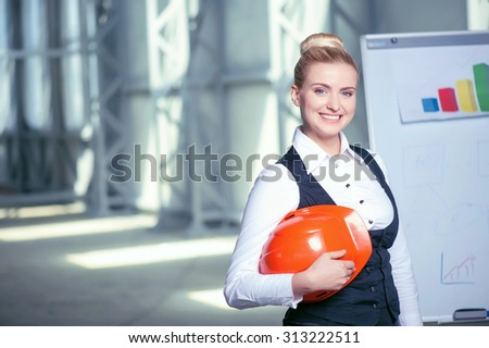 Attractive female architect is creating a new project. She is standing near board with sketches of construction. The woman is looking forward and smiling. Copy space in left side - stock photo