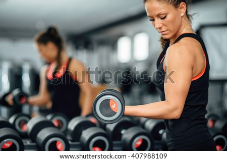 Attractive female athlete exercising in modern gym. Toned image, focus on dumbbell - stock photo