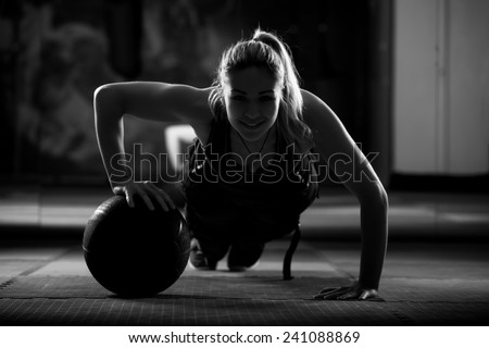 Attractive female athlete performing push-ups on medicine ball.Medicine ball push up.Low key - stock photo