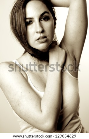 Attractive female brunet  looking at the camera with hair wrapped around the neck, b&w