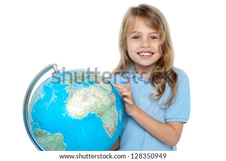 Attractive female child pointing out her holiday destination on the globe. - stock photo