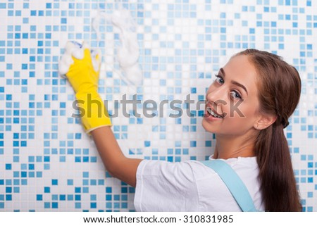 Attractive female cleaner is doing clean-up in bathroom. She is scrubbing a tiled wall with a sponge. The woman is looking at the camera and smiling - stock photo