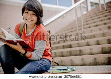 attractive female college student sitting on stairs