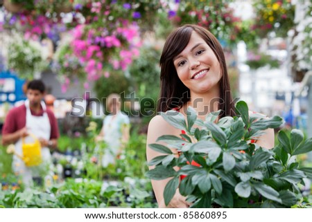 Attractive female customer holding potted plant with people in background