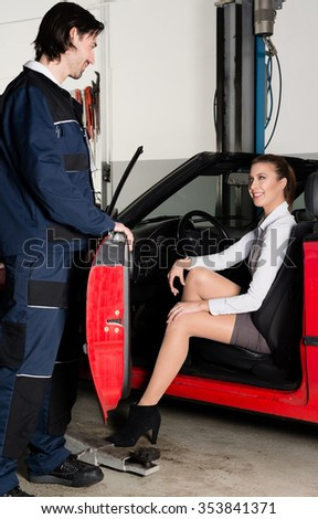 Attractive female customer is getting out of her car in a garage with mechanic openig the driver door - stock photo
