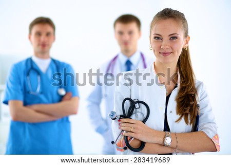 Attractive female doctor in front of medical group - stock photo