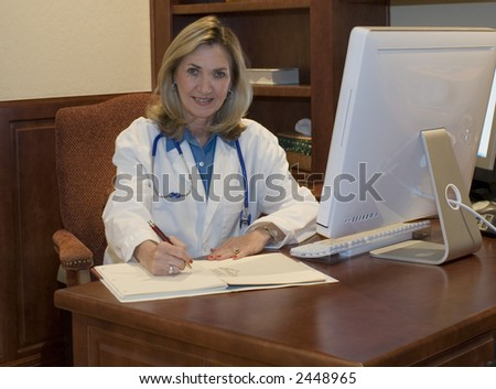 attractive female Doctor sits at desk writing