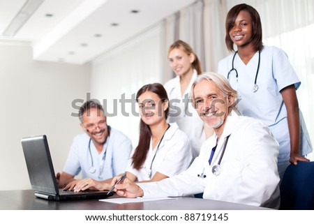 Attractive female doctor working on her laptop with healthcare colleagues in her office - stock photo