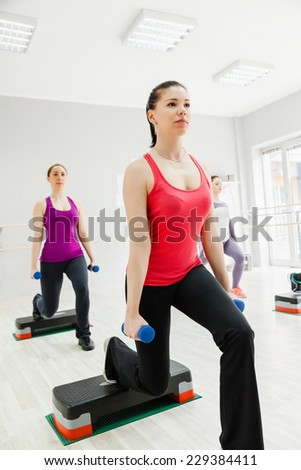 Attractive Female Doing Step Aerobics Exercise With Dumbbells
