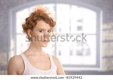 Attractive female dressed for workout standing front of window.? - stock photo