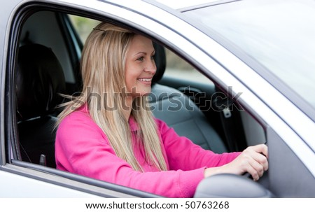 Attractive female driver at the wheel in her new car - stock photo