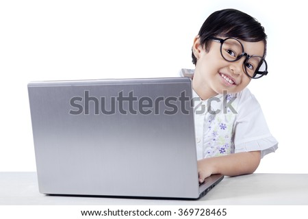 Attractive female elementary school student smiling at camera and using a laptop, isolated on white background - stock photo