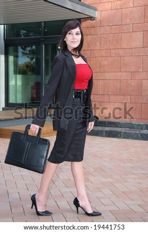 Attractive female executive in red top and black suit outside office building