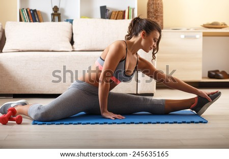 Attractive female exercise at home.Fitness.She stretching her legs. - stock photo