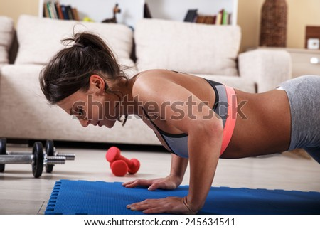 Attractive female exercise in her living room.She doing push ups. - stock photo