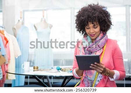 Attractive female fashion designer using digital tablet - stock photo