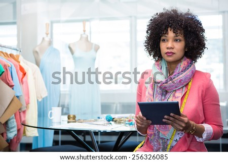 Attractive female fashion designer using digital tablet - stock photo