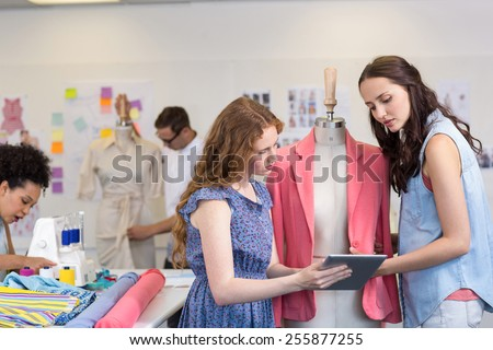 Attractive female fashion designers using digital tablet - stock photo