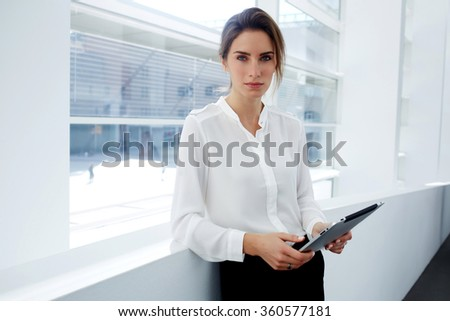Attractive female financier dressed in formal wear checks own schedule work on digital tablet during break, young serious businesswoman using touch pad while standing in office interior near window - stock photo