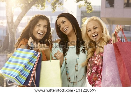 Attractive female friends holding shopping bags, smiling happy outdoors. - stock photo