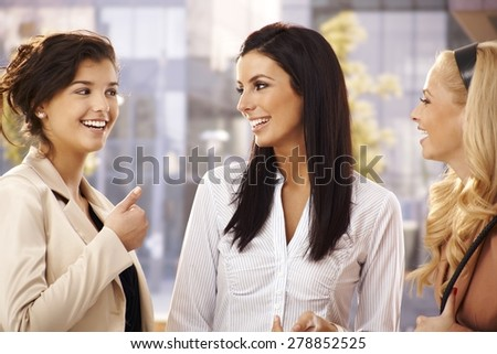 Attractive female friends talking, smiling outdoors. - stock photo