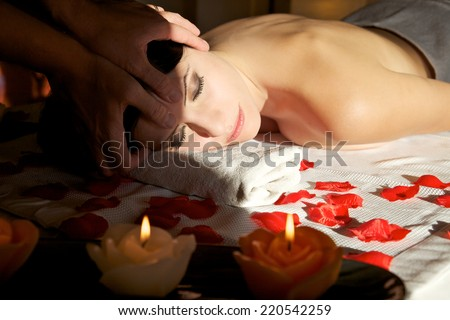 attractive female getting recreation massage of head with closed eyes at spa salon - stock photo