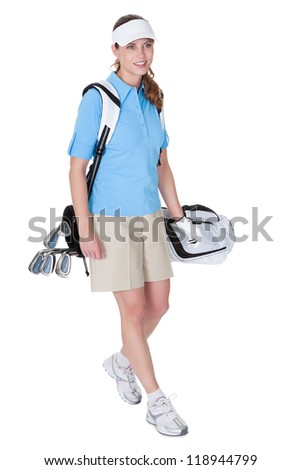 Attractive female golfer in golf clothing with a bag of clubs selecting an iron isolated on white - stock photo