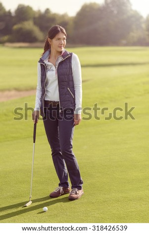 Attractive female golfer standing on the green with her putter, looking away with concentration to the next strike - stock photo