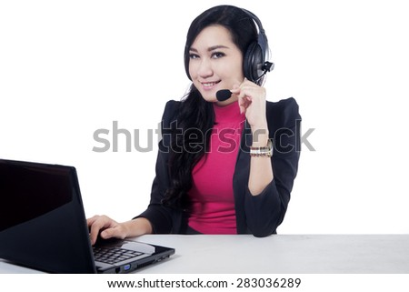 Attractive female help desk smiling on the camera while working with laptop and headset, isolated over white - stock photo