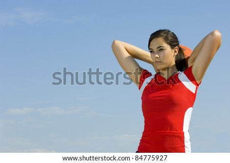 Attractive female holding a basketball while playing outdoors in summer - stock photo
