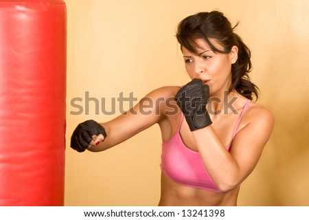 Attractive female kickboxing with red punching bag - stock photo