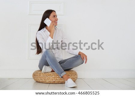 Attractive female looking off into the distance on her left while talking on the phone