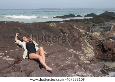Attractive female lying ont he rocks of a beach catching a tan - stock photo