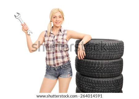 Attractive female mechanic holding a huge wrench and standing next to a stack of tires isolated on white background - stock photo