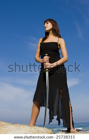 Attractive female model holding a samurai sword - stock photo