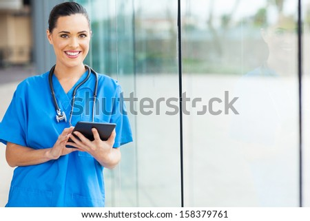 attractive female nurse using tablet computer at hospital - stock photo