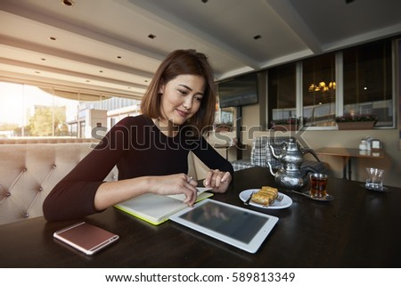 Attractive female owner of business enterprise recreating with cup of coffee making checklist of ideas and operation to increase income from realization products developing strategy of working