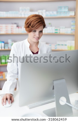 Attractive female pharmacist checking information standing reading a large computer monitor on her desk in the pharmacy - stock photo