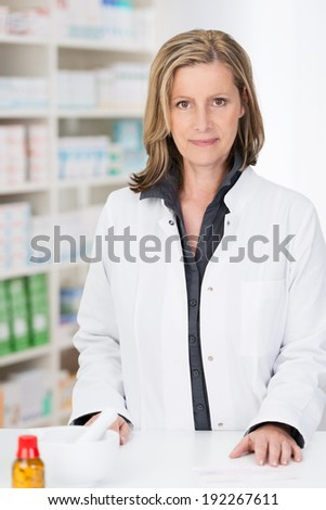 Attractive female pharmacist standing behind the counter in her pharmacy looking at the camera with a smile against a backdrop of stocked shelves - stock photo