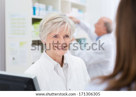 Attractive female pharmacist with a warm welcoming smile helping a patient in the pharmacy while her colleague works in the background - stock photo