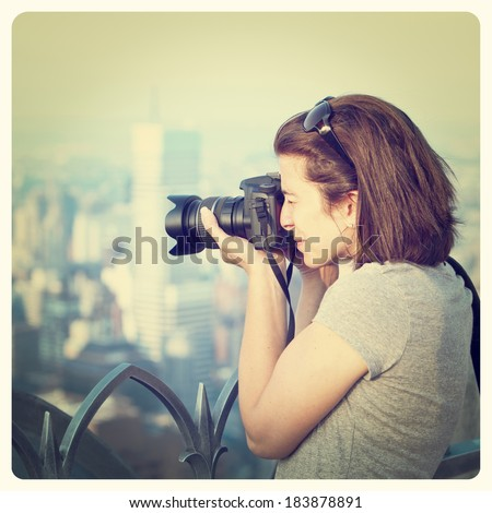 Attractive female photographer at sunset on top of a skyscraper with Instagram effect filter - stock photo