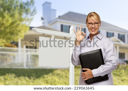 Attractive Female Real Estate Agent in Front of Blank Real Estate Sign and House. - stock photo
