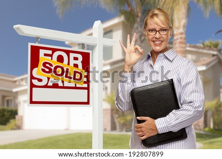 Attractive Female Real Estate Agent in Front of Sold Home For Sale Sign and House.