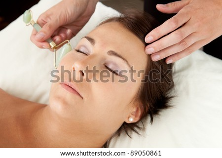 Attractive female reciving face massage with jade roller at acupuncturist - stock photo
