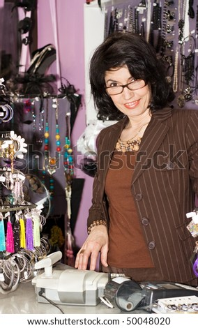 Attractive Female sales clerk behind the cash register - stock photo