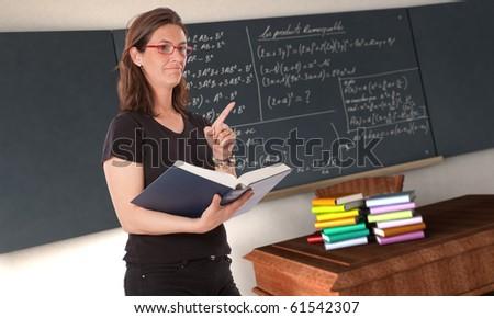 Attractive female teacher teaching in a classroom - stock photo