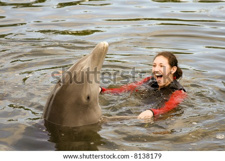 Attractive Female Teenager is Swimming with the Dolphins - stock photo