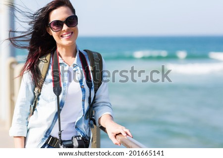 attractive female tourist standing on pier