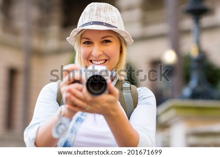 attractive female tourist taking picture with digital camera - stock photo